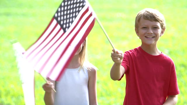 Two children waving American flags Two children, an 8 year old girl and her 9 year old brother standing outdoors, waving American flags on a sunny day. They are smiling and looking at the camera. family 4th of july stock videos & royalty-free footage