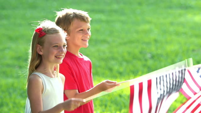 Two children waving American flags