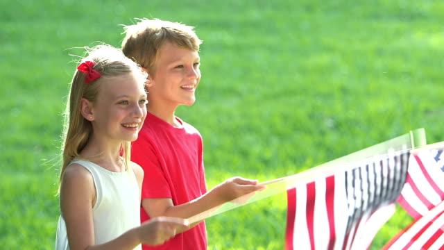 Dos niños agitando banderas americanas - vídeo
