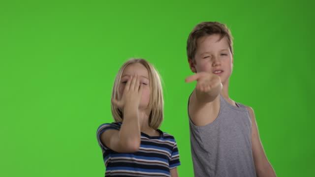 två childs blåser en puss till kamera framför greenscreen - blåsa en kyss bildbanksvideor och videomaterial från bakom kulisserna