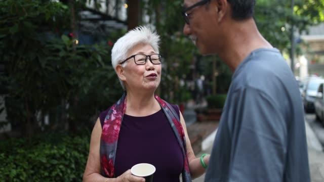 stockvideo's en b-roll-footage met twee chinese senior volwassenen in het park - aziatische etniciteit