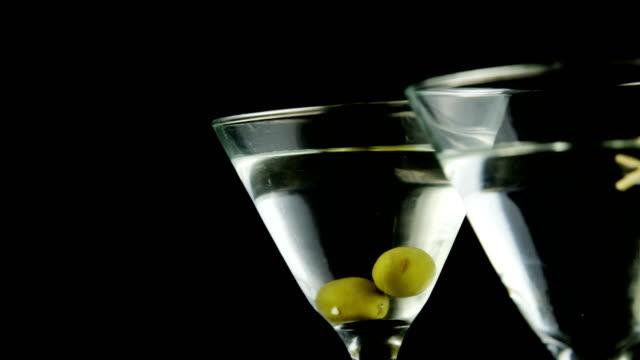 stockvideo's en b-roll-footage met twee cocktail glazen gegarneerd met groene olijven - martiniglas