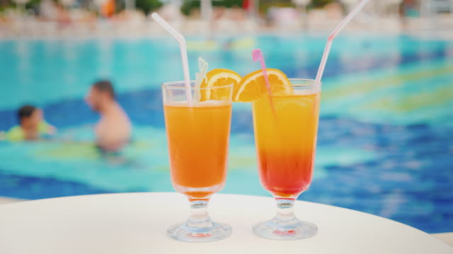 vídeos de stock e filmes b-roll de two cocktails with straws on the background of the pool. the pool blurred contours father teaches his daughter to swim. holiday with children in a luxury resort concept - cocktail