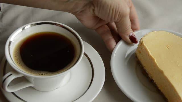 Two coffee and two plates with cheesecake a woman prepares a delicious Breakfast