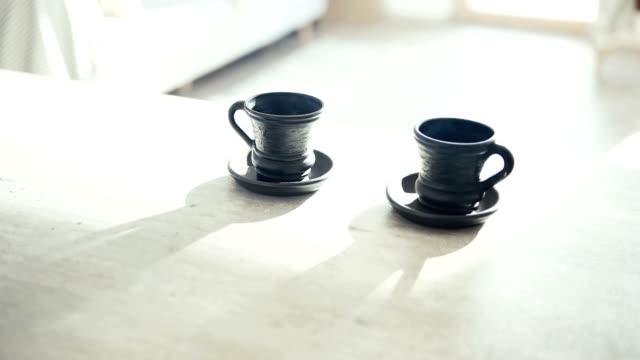 due tazze nere di argilla caffè sul tavolo con retroilluminazione luminosa che attira lunghe ombre di tazza. caffè per coppia in moderne riprese cinematografiche concettuali di cucina. - due oggetti video stock e b–roll