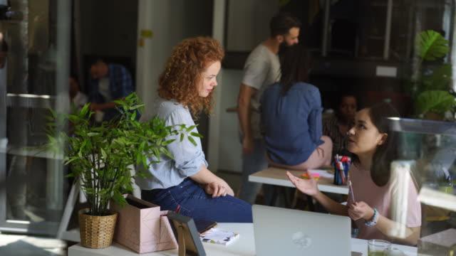 zwei kollegen plaudern in der kaffeepause im co-working-space - klatsch stock-videos und b-roll-filmmaterial