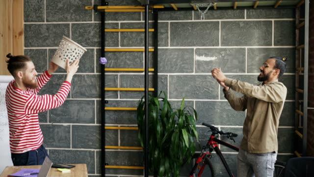 två kollegor ha kul att spela basketmatch kasta papper i soptunna i moderna kontor - basketboll boll bildbanksvideor och videomaterial från bakom kulisserna
