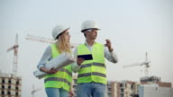 istock Two colleagues of engineers a man and a woman discussing a drawing and a tablet computer on the background of buildings under construction and cranes, a woman talking on the phone with the boss. 1169101249
