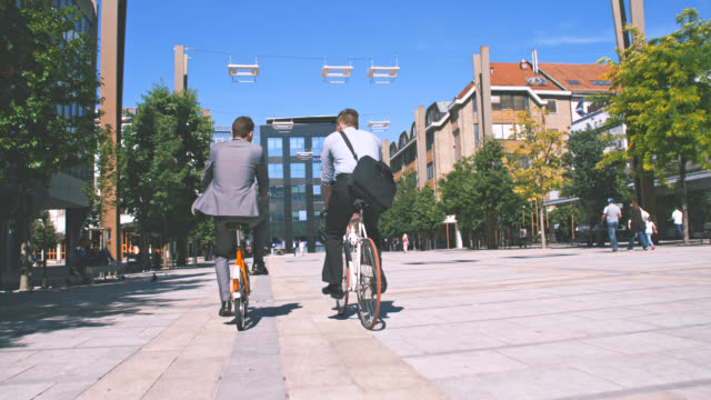 SLO MO Two colleagues riding their bicycles to work video