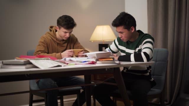 vídeos y material grabado en eventos de stock de dos estudiantes universitarios sentados a la mesa con libros y libros de trabajo. chico asiático estudiando como su amigo caucásico usando teléfono inteligente. educación, deberes, estilo de vida. - solteros jóvenes