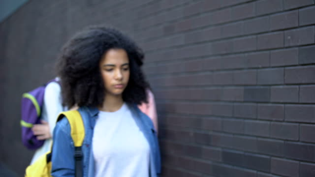 Two college teenagers mocking black schoolgirl, laughing at classmate appearance