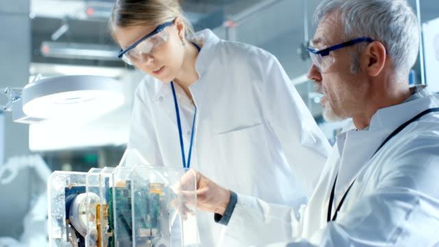 Deux informaticiens choisissent entre la carte de Circuit imprimé pour travailler avec. En arrière-plan, technologiquement avancée Centre de recherche scientifique. - Vidéo