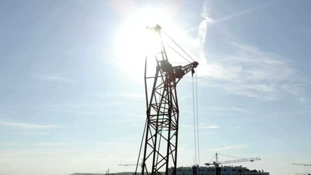 Two construction cranes on the background of blue sky and the sun, which shines in the camera hiding behind the construction crane