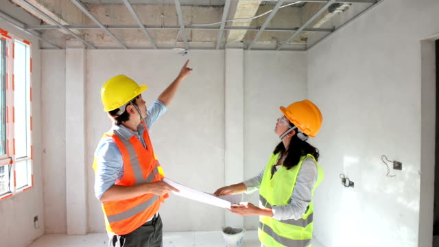 Two construction engineers working together in side building planning for the ceiling