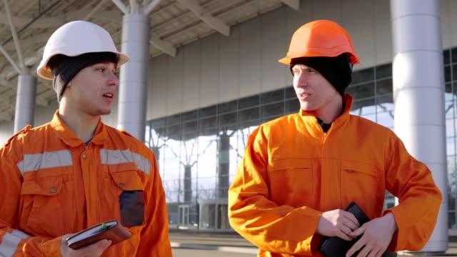 vidéos et rushes de deux travailleurs de la construction en uniforme orange et casques marchant dans le domaine de la construction et de la recherche sur les plans d'ensemble. bâtiment à l'arrière-plan - uniforme