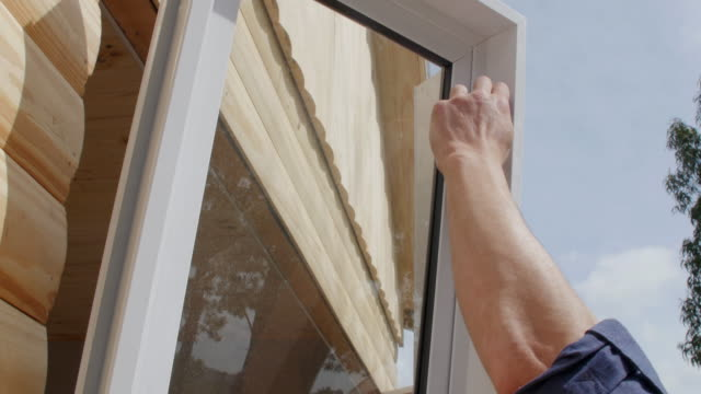 Two construction workers installing window on a new house Two construction workers are installing a window on the opening of a new house craftsman architecture stock videos & royalty-free footage