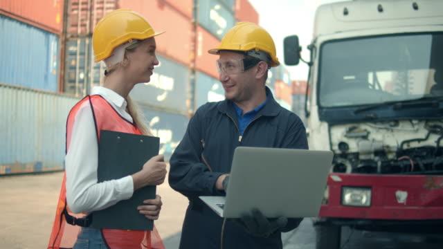 två containerterminalanställda som pratar och använder laptop - wine box bildbanksvideor och videomaterial från bakom kulisserna