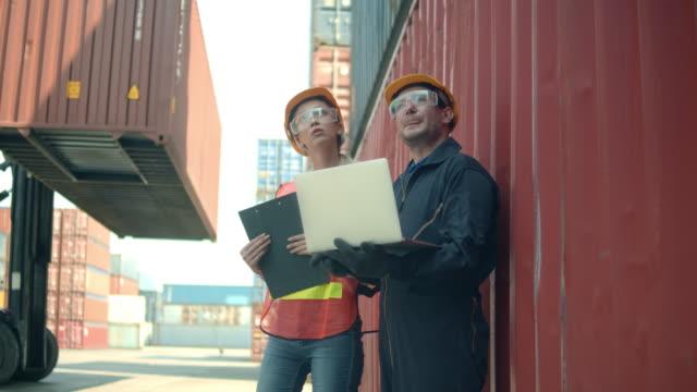 vídeos de stock, filmes e b-roll de dois funcionários do terminal de contêineres conversando e usando laptop - vinho do porto