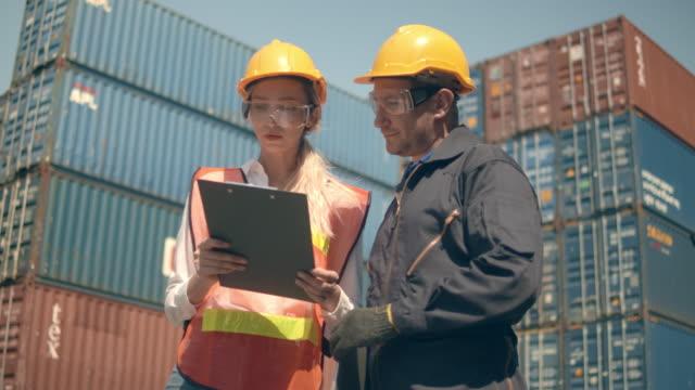 vídeos de stock, filmes e b-roll de dois funcionários do terminal de contêineres trabalhando e conversando em frente a pilhas de contêineres de carga coloridas no porto marítimo - vinho do porto