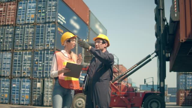 två containerterminalanställda som arbetar och pratar framför färgglada lastcontainerstackar i sjöfartshamnen - wine box bildbanksvideor och videomaterial från bakom kulisserna