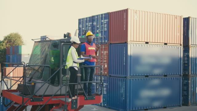 två containerterminalanställda som arbetar och pratar i frakthamn - wine box bildbanksvideor och videomaterial från bakom kulisserna