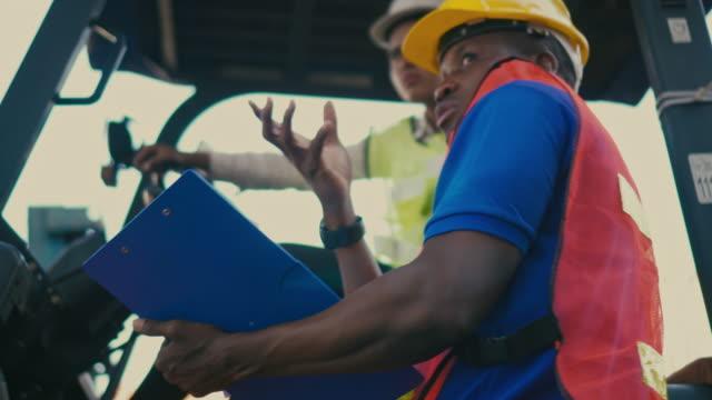 vídeos de stock, filmes e b-roll de dois funcionários do terminal de contêineres trabalhando e conversando no porto marítimo - vinho do porto