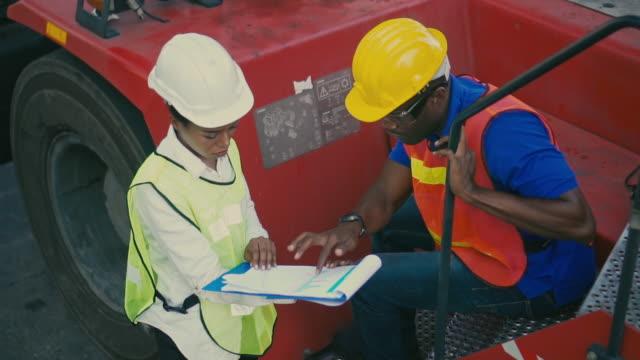 vídeos de stock, filmes e b-roll de dois funcionários do terminal de contêineres trabalhando e falando no porto de transporte, câmera lenta - vinho do porto