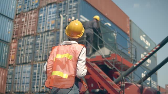 två containerterminalanställda som arbetar framför färgglada lastcontainerstackar i sjöfartshamnen - wine box bildbanksvideor och videomaterial från bakom kulisserna