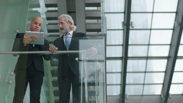 two corporate executives standing and talking in modern building video