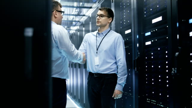 Two Corporate Workers Shake Hands in Greeting. They're Working in Modern Data Center with Rows of Server Racks. Two Corporate Workers Shake Hands in Greeting. They're Working in Modern Data Center with Rows of Server Racks. Shot on RED EPIC-W 8K Helium Cinema Camera. it professional stock videos & royalty-free footage