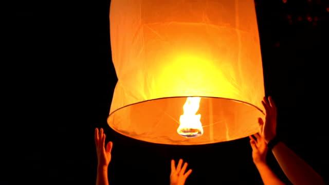 two couple hands release floating sky lantern to the sky - китайский фонарь стоковые видео и кадры b-roll