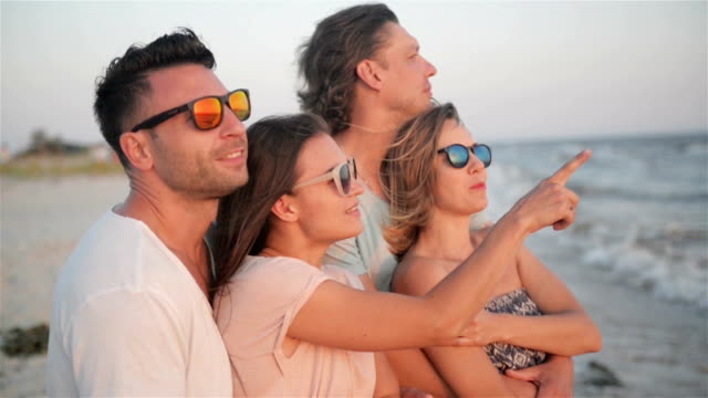 Two Couples are Looking at the Sunset Spending Time Together on the Seaside during Windy Weather video