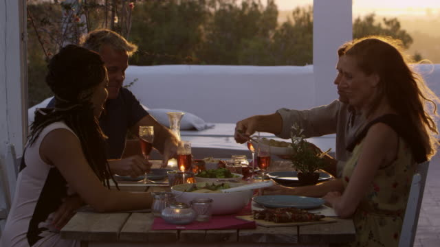 Two couples eating dinner at a table on a rooftop terrace, shot on R3D video