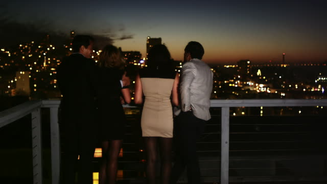 Two couples look over a balcony while hanging out at a rooftop bar at dusk Two couples look over a balcony while hanging out at a rooftop bar at dusk party social event stock videos & royalty-free footage