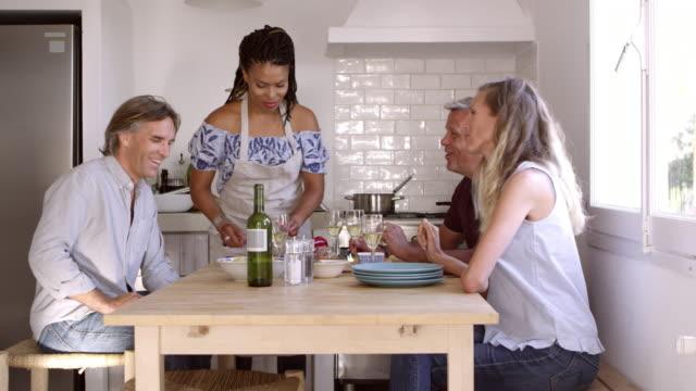 Deux couples porter un toast à une table de la cuisine, vue de côté, tourné sur R3D - Vidéo