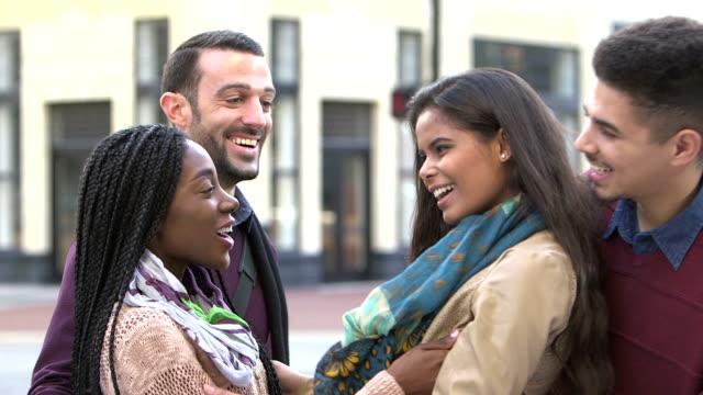 Con a dos parejas, abrazan a las mujeres en la calle de la ciudad - vídeo