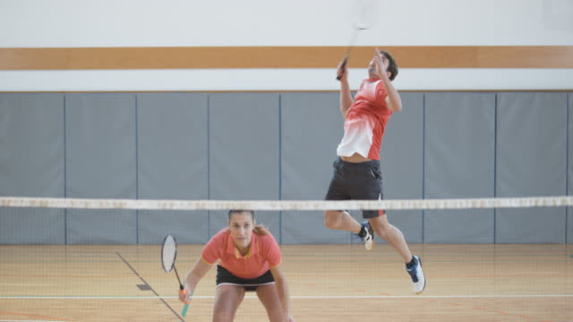 Two couples playing indoor badminton video