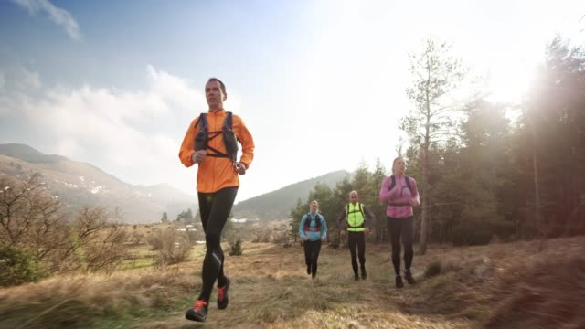 Two couples running in the mountains on a sunny day in spring
