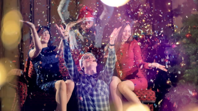 Two couples sit near a Christmas tree and play with confetti. video