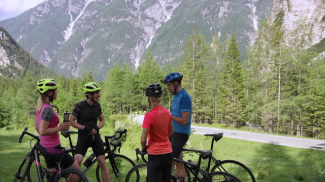cs two couples standing next to their road bikes above a mountain road and taking a break while enjoying the view - ciclismo su strada video stock e b–roll