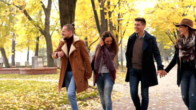 Two couples walking together Two young caucasian cute couples walking together in public park and having a nice time. girlfriend stock videos & royalty-free footage