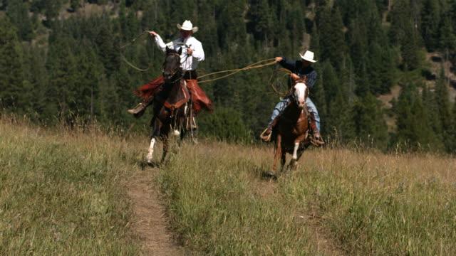 Dos cowboys riding a caballo swinging lassos, slow moiton - vídeo