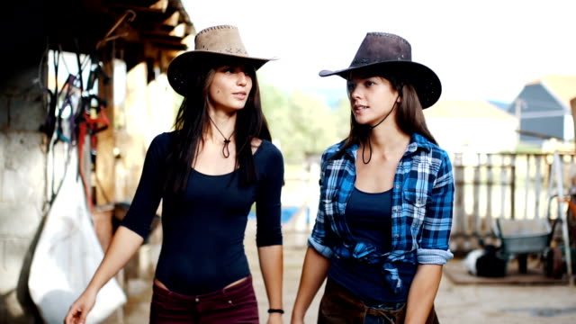 Two cowgirl sisters are inspection their stable video