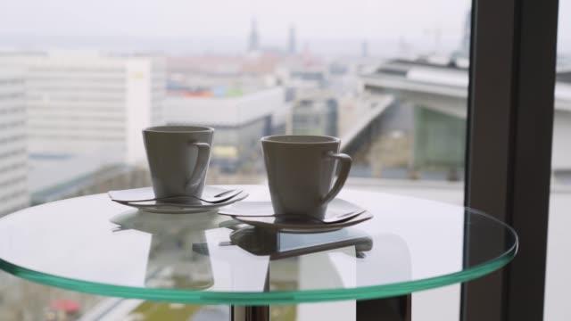 大きな窓に対するガラステーブルの上の2つのカップ - マグカップ点の映像素材/bロール
