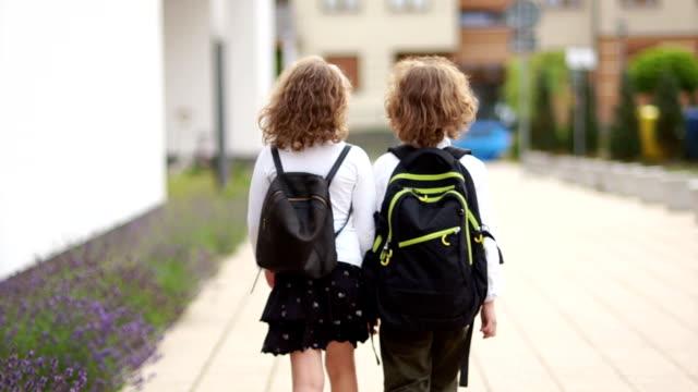 男の子と女の子、2 つ、中小学生は、バックパックで学校へ行きます。背面図。学校に戻って知識の日 - 新学期点の映像素材/bロール