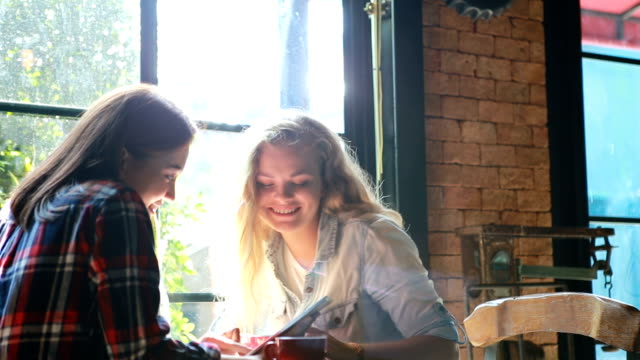 two cute beautiful happy girl smile and gossiping in the cafe in the city with cups of coffee during sunny day