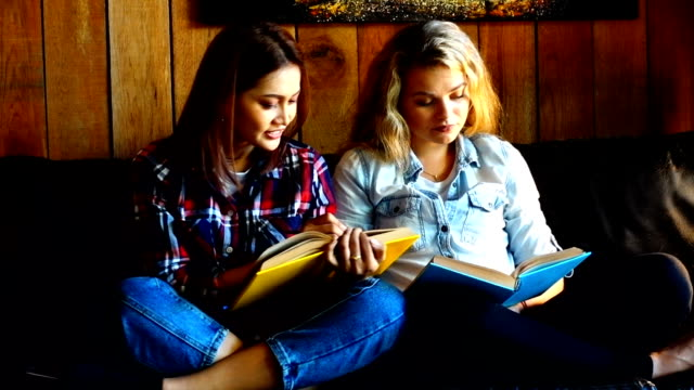 two cute beautiful happy girl smile and gossiping reading a book in the cafe in the city  during sunny day