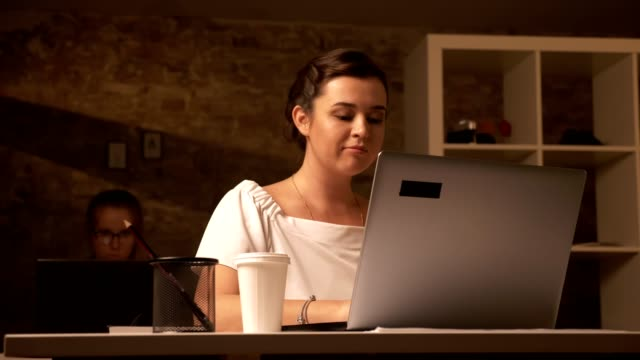 Two cute caucasian working girls sitting next to laptops, typing, one focused woman is drinking coffee in brick office Two cute caucasian working girls sitting next to laptops, typing, one focused woman is drinking coffee in brick office. large build stock videos & royalty-free footage