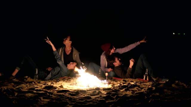 2 つのかわいいカップルは焚き火で夜遅くまで座っていると星を見て ビデオ
