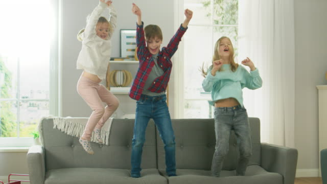 two cute little girls and young adorable boy have fun, jumping high on a couch at home. happy children playing in the sunny living room. in slow motion. - skakać filmów i materiałów b-roll